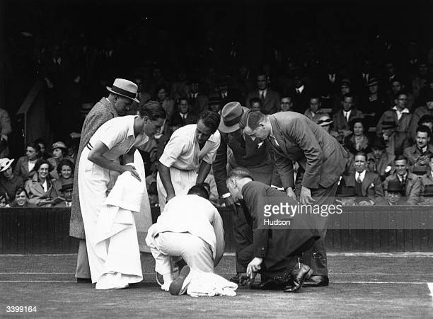 Officials attending to the ankle of Australian tennis player Adrian Quist after he fell during his Davis Cup semi-final match against Gottfried von...