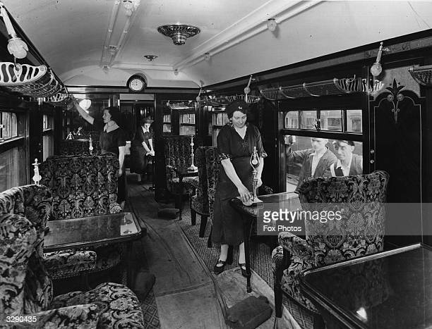 Cleaners at work in the luxurious coach 'Minerva' where the King and Queen will travel to Paris