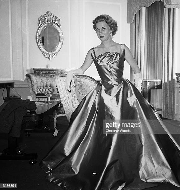 A lady standing in Harrods department store London wearing a shimmering fulllength ball gown