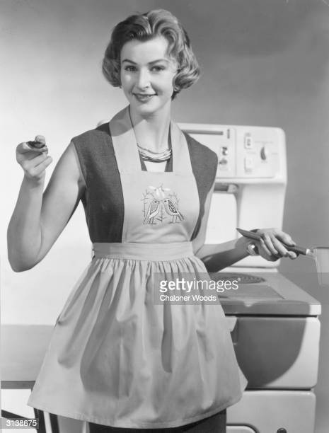 A young housewife stands in her model kitchen wearing an apron She holds a saucepan in one hand and offers a spoonful of the supper she has cooked...