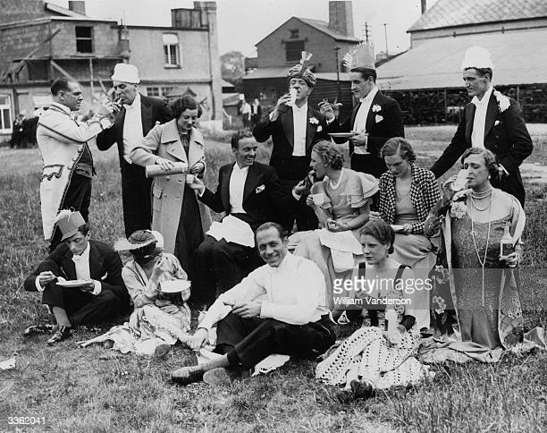 American film actor Douglas Fairbanks Junior receives a drink from a flask whilst dining al fresco with the cast of the film 'Gay Love'.