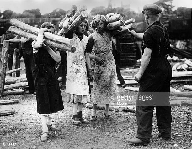 Women employed carrying props which are graded before stacking.