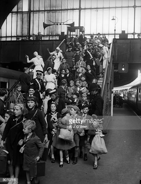 Police and VAD nurses shepherd a crowd of young evacuees onto their trains at Paddington Station, London, en route to the comparative safety of the...