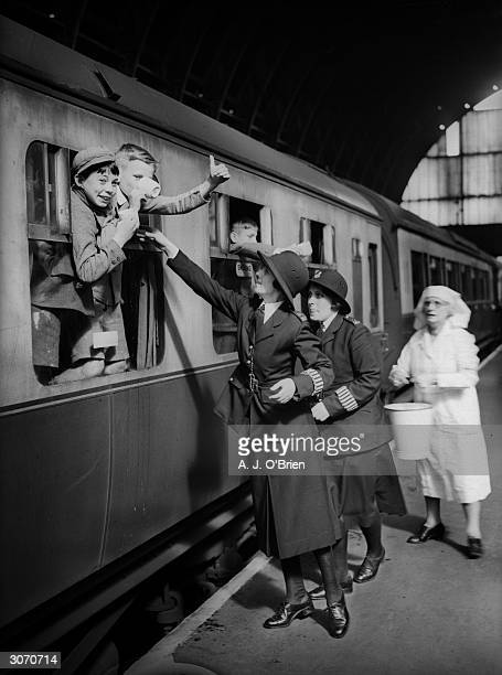 Two policewomen and a VAD nurse serve refreshments to the young evacuees before their departure from London to the comparative safety of the...