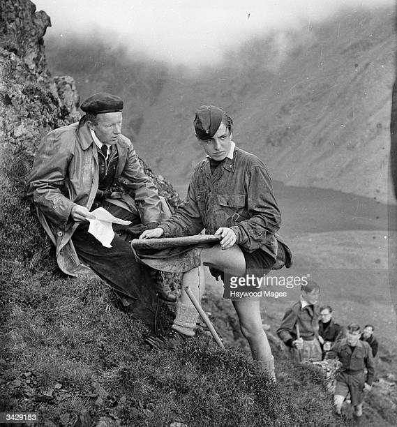 An officer of the Aberdovey Outward Bound Sea School asks student Dieter Jung to pinpoint their position on the map whilst on a walk over Cader...
