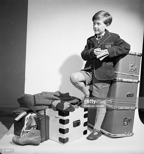 Young schoolboy with his possessions packed into a trunk and a couple of suitcases.