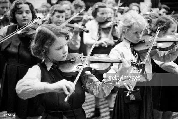 Young pupils at the Glasgow High School for Girls playing their violins in the school orchestra Garnethill Public School became the Glasgow High...