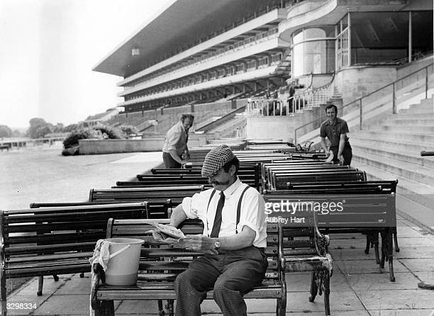Ascot ground staff, two at work cleaning benches and one taking a break, reading a newspaper.