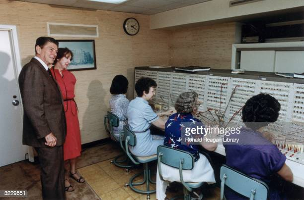 President Ronald Reagan stands with a woman, observing operators working at the switchboard at the Old Executive Office Building, Washington, DC.