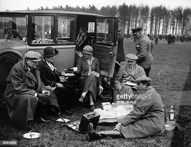 From left to right Colonel Fox Pitt Mrs Hambre Mrs and Major Neville and Colonel Hambre sit down to a picnic between events at the Newmarket and...