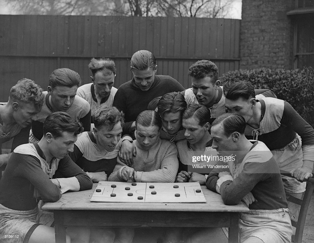 Joey Carr (centre), a fly weight boxer studying football tactics on a demonstration board with members of St Marks' Fellowship unemployed football team whom he is coaching. They are in the final of the London Occupational Shield (the unemployed Cup Final) to be played at Wembley.