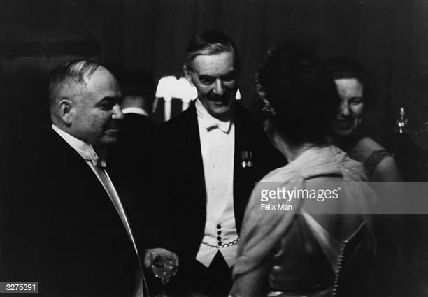 The Russian Ambassador to Britain Ivan Mikhailovich Maisky and British Prime Minister Arthur Neville Chamberlain talk at a party given in the USSR...