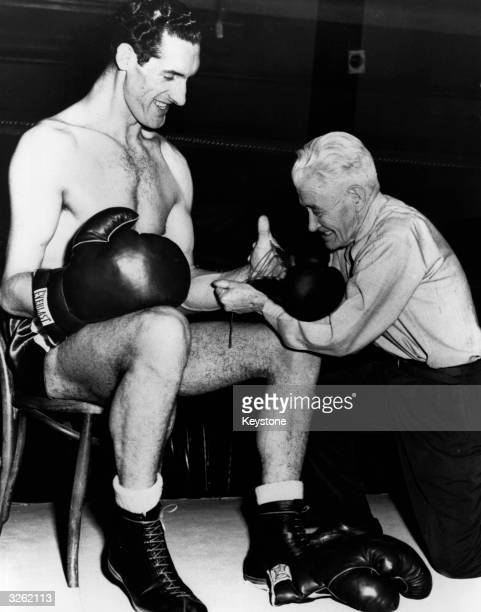 Tall Irish boxer Jim Cully 7ft 2ins from Tipperary smiles as a US boxing authority 'Pop' Gleason attempts to put a regulationsized glove on his big...