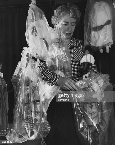 Ann Hogarth director of 'Master Peter's Puppet Show' packing away the stars of the show in protective bags before they take part in the 'Glyndebourne...