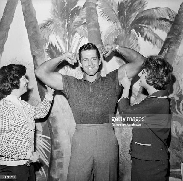 American actor Gordon Scott best known for his portrayal of Tarzan in the 1950s flexes his muscles for a couple of female admirers
