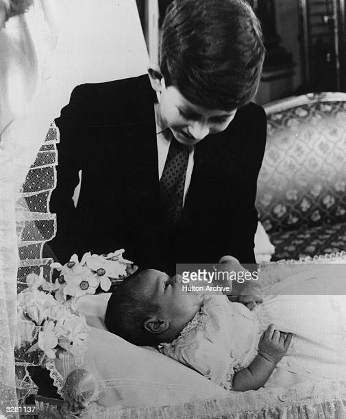 Prince Charles admiring his baby brother Prince Andrew shortly after his birth