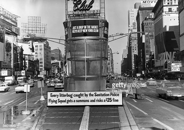 A gigantic litter basket in Times Square New York with a sign saying 'Just a Drop in the basket keeps new York Clean' Another signe threatens a 25...