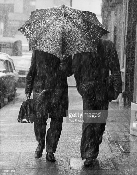 Two city gents one caught without his overcoat walking in Farringdon Road share an umbrella as snow falls across London