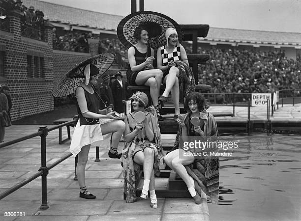 A group of young women wearing the latest in bathing fashions put on their makeup beside a pool at a Southport holiday camp Merseyside