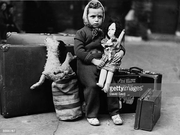 Little girl waiting nervously with her doll and luggage, before leaving London for her billet, during the Second World War.