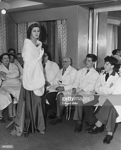New Zealand born fashion model Fiona Campbell-Walter models 'Gloriana', a white mink stole, for members of staff at the rehearsals for a fashion show...