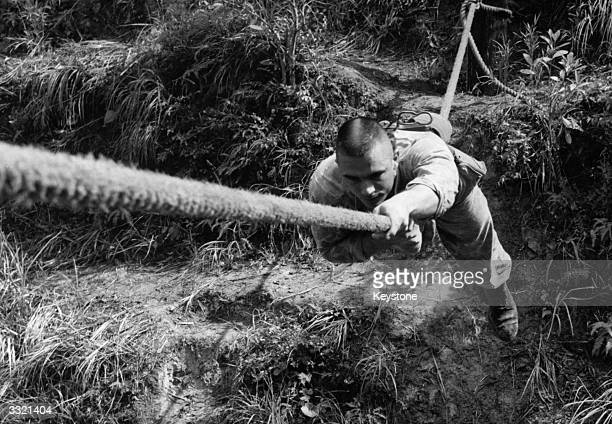 An American soldier crossing a ravine using a single rope as he learns jungle warfare techniques at a jungle training school in the hills of Okinawa...