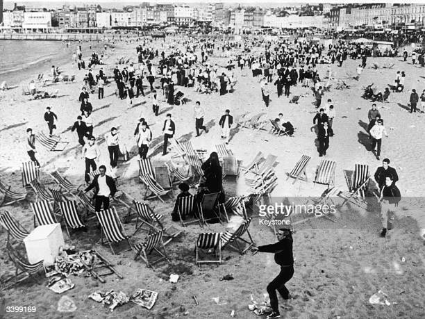Mods invading the beach at Margate Kent waving sticks and throwing bottles at retreating Rockers