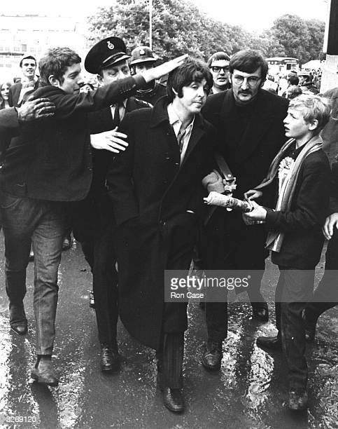 Pop singer and bass player Paul McCartney of The Beatles is besieged by fans as he arrives at Wembley to see the FA Cup Final football match between...