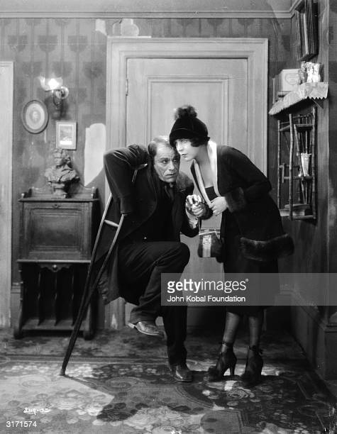 American actor Lon Chaney masquerades as a cripple in the presence of Renee Adoree in a scene from 'The Blackbird' directed by Tod Browning