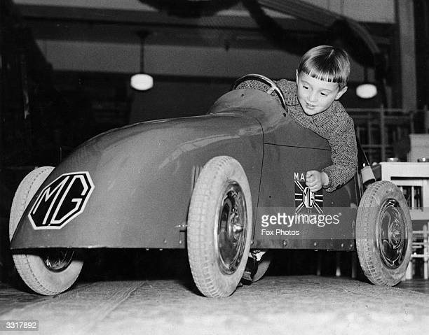 A young boy trying out a toy MG Midget car at the famous toy shop Hamleys on Regent Street London