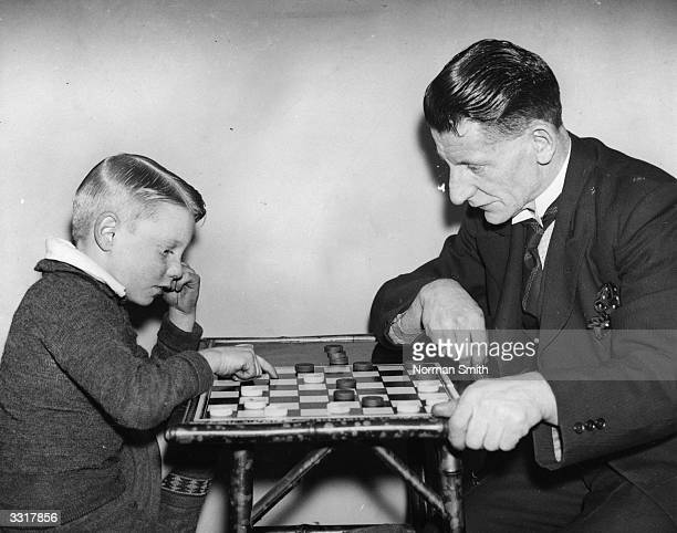 Six year old Dennis Page an expert at draughts playing his father who is no match for him