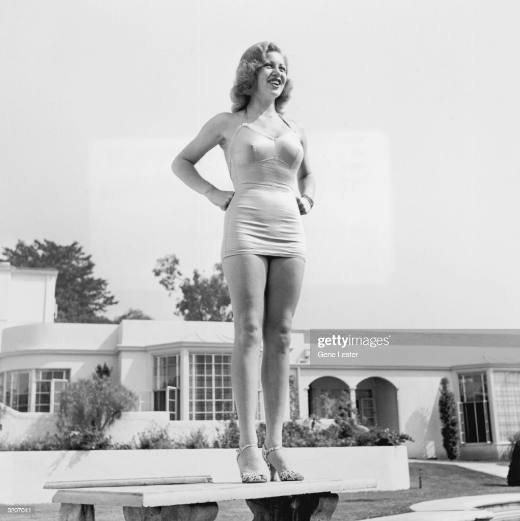 Full-length image of actor Lana Turner standing on a bench and wearing a swimsuit at her Sunset Plaza Apartment complex, Los Angeles, California.