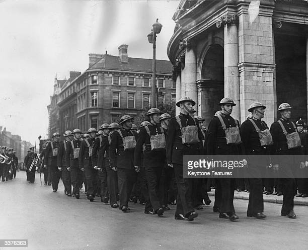 The Garda the Irish police force on parade with their gas masks and tin helmets