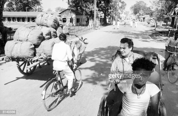 Daily Express press photographer, Terry Fincher, in the back of a rickshaw while on assignment in India.