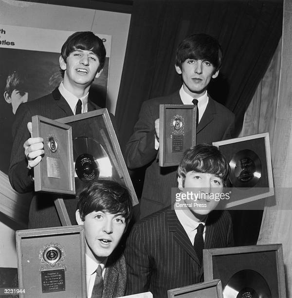 The Beatles holding their silver LP and EP discs presented to them by EMI records in London to mark sales of records including the LP 'Please Please...