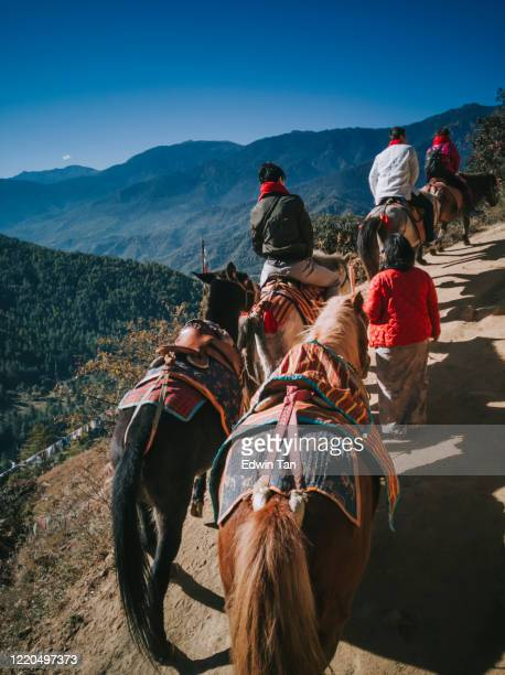 18th november 2017 a group of tourist riding donkey and horse upward hill to tiger nest in bhutan rear view on dirt road - bhutan stock pictures, royalty-free photos & images