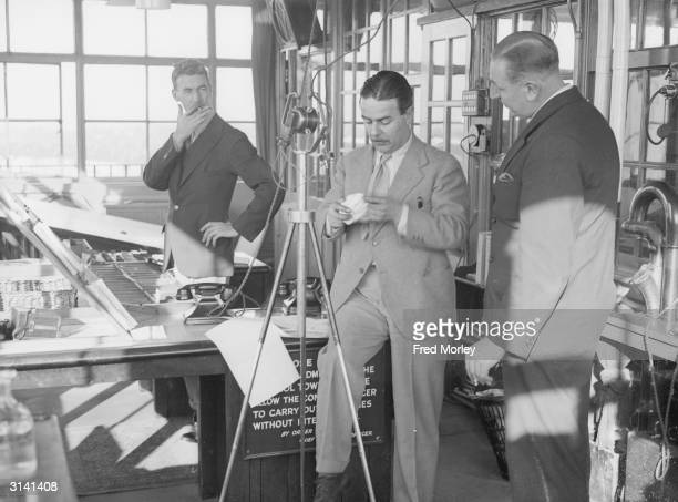BBC commentator Norman Shelley at the microphone in the control tower at Croydon Airport With him is James Jeff the control officer Norman Shelley...