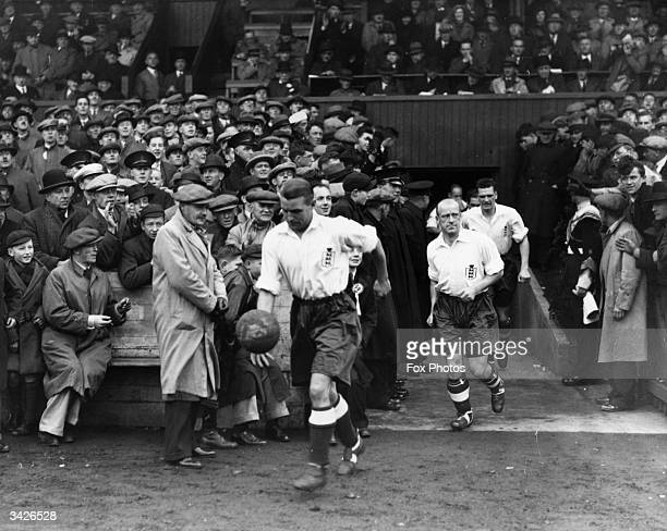 The Arsenal and England captain Eddie Hapgood leading the England team out onto the pitch at Belfast before an international match
