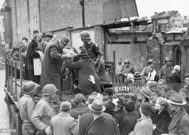 German civilians boarding a lorry in Aachen bound for a Belgian refugee camp to escape the battle for the city between German and American forces