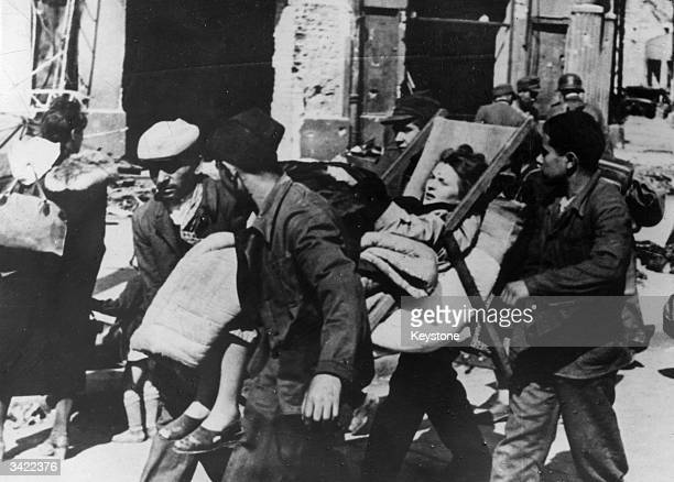Relatives carry a seriously ill woman in a deckchair following the failure of the Warsaw Uprising. German soldiers, searching the ruins of the city...
