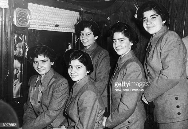 A portrait of the Dionne quintuplets standing in the corridor of a train approaching Grand Central Station New York City New York