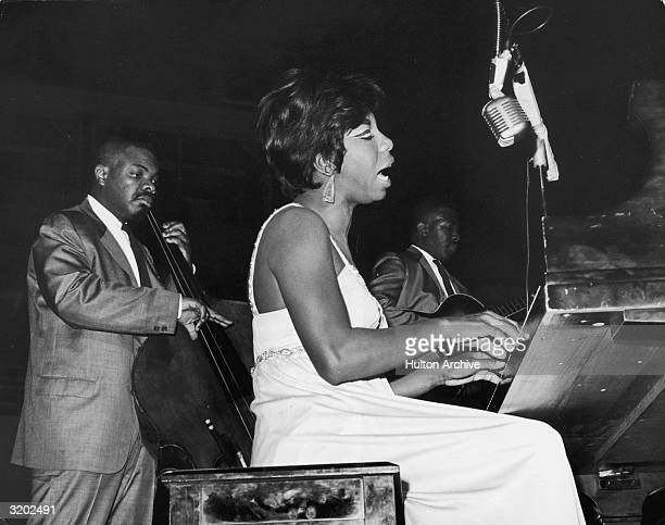 American pianist and vocalist Nina Simone sings while playing piano at the World's Fair Singers' Bowl Queens New York A bassist and a guitarist play...