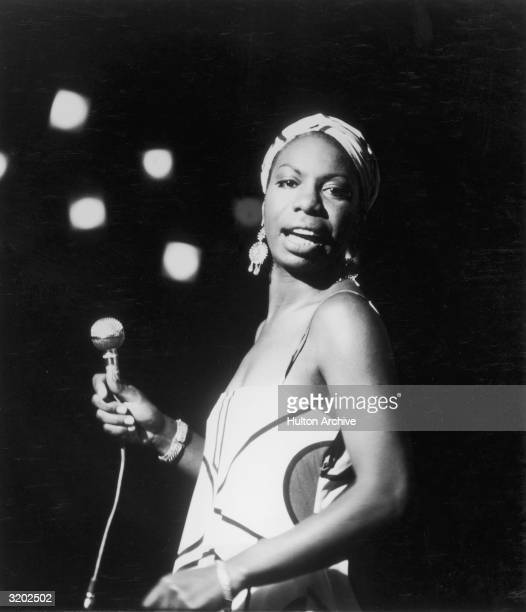 Portrait of American pianist and jazz folk and gospel singer Nina Simone looking over her shoulder while performing Simone is wearing a slip dress...