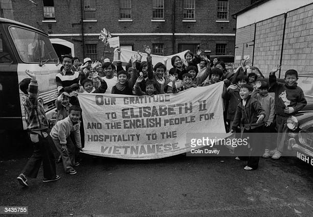 Group of Vietnamese boat people hold a large banner saying, 'Our Gratitude to Elisabeth II and the English people for hospitality to the Vietnamese...