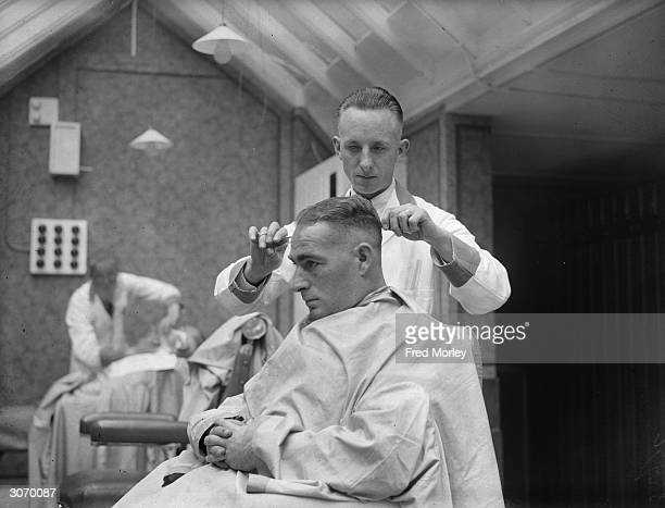 New Zealand batsman 'Stewie' Dempster' checking a client's haircut in a barber's shop which he has opened in Blackpool