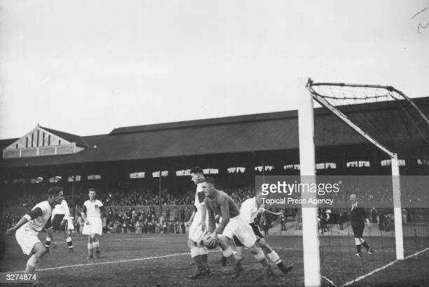 Hetherington the Burnley goalkeeper eludes Perry the Fulham centre forward during a match at Craven Cottage Fulham