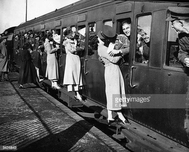 Soldiers kissing their sweethearts goodbye as troops leave for Egypt from Feltham Station.