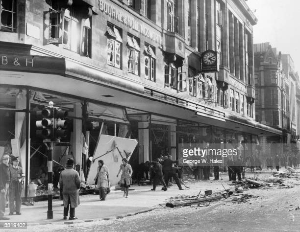 Shop assistants assist ARP staff to clear debris from damaged windows at Bourne Hollingsworth's department store in London's West End after a German...