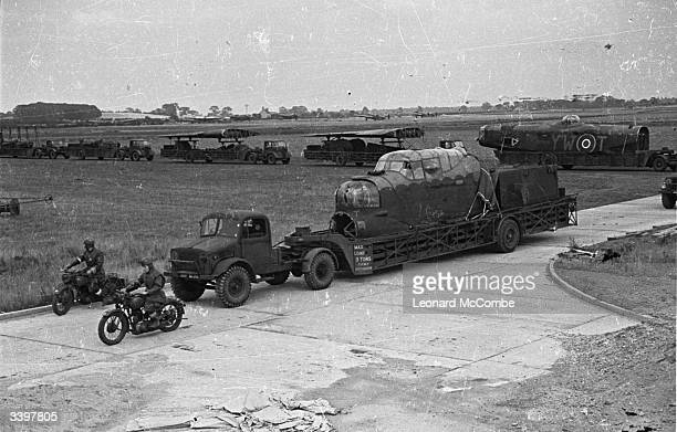 RAF Repair and Maintenance Service workers remove a shotup crashed Lancaster bomber from the runway in separate pieces Original Publication Picture...