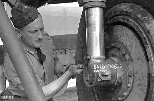 British mechanic at work on the wheel of an aircraft during the Berlin Airlift. Original Publication: Picture Post - 4643 - The Strain Of The Airlift...